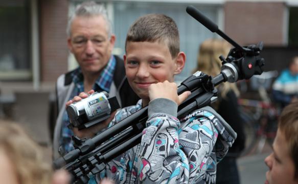 Jongen houdt groot camerastatief vast tijdens de film workshop van Edutones